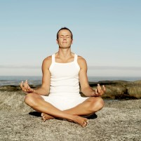 Man Meditating on a Rock at the Beach --- Image by © Royalty-Free/Corbis